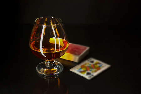 Cognac glass and playing cards. Cognac glass. Brandy glassful. Cognac france. Playing cards and scotch drink. Reklamní fotografie