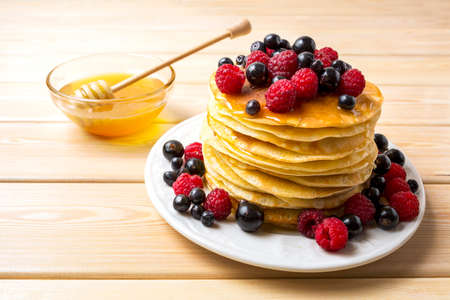 Pet pancakes with honey and fresh berries. Stack of breakfast pancakes served with blueberry, raspberry and blackcurrant. Stock fotó