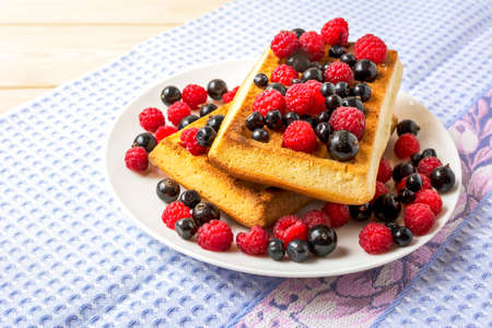 Belgian waffles with blueberry, raspberry and blackcurrant. Breakfast waffles with fresh berries.
