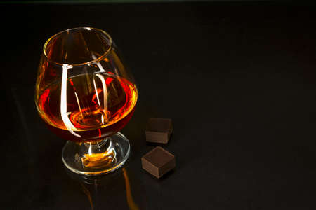 Cognac glass and chocolate on black background. Brandy glass. Cognac glass. Whiskey glass. Cognac france.