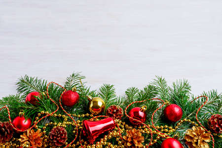 Christmas background with pine cone, golden and red decors. Christmas party decoration with shiny balls. Christmas greeting background. Copy space. 写真素材