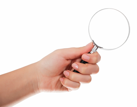 Female hand holding the magnifying glass isolated on white background Stock Photo
