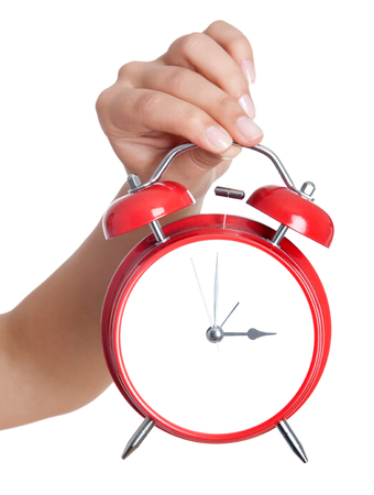 Closeup shot of a woman holding red heartshape alarm clock. Close up of female hands holding a red alarm clock. Shallow depth of field with focus on the alarm clock.