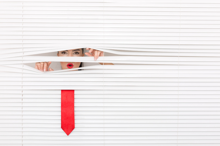 jalousie: Portrait of a woman looking through out the blinds