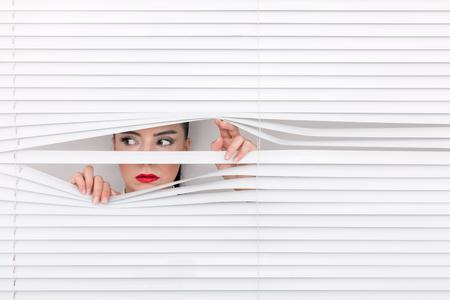 Retrato de una mujer mirando a través de las persianas Foto de archivo - 73212963