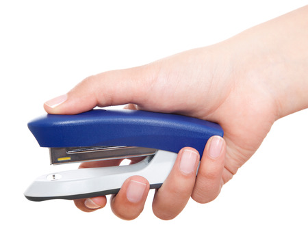 Hand holding blue stapler stapling papers closeup view Stock Photo