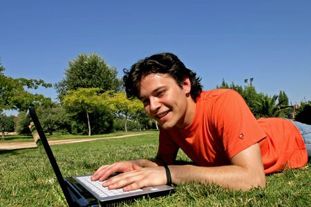 smiling young man lying in the grass and working with a laptop