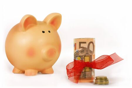 bankroll: piggy bank and bankroll with a red ribbon isolated in white background Stock Photo
