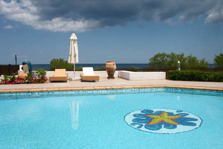 swimming pool with sunshade on the seaside Stock Photo