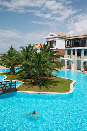 swimming pool with palm tree in tropical hotel Stock Photo