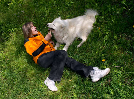 mirth: Cheerful girl plaing with merry dog on the grass