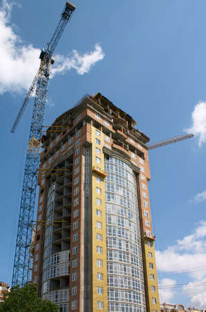 housebuilding: building under construction and hoisting crane