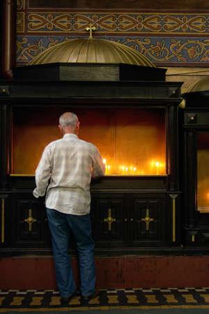 man with burning candle in catholic churche Stock Photo