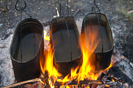Three kettles warming in the fire in camping Stock Photo