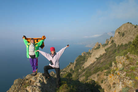 Happy girls standing on the peak above the sea Stock Photo