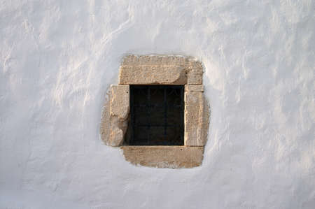 small window with grate in white lime wall Stock Photo