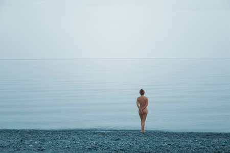 Lonely naked girl on the beach of quite sea
