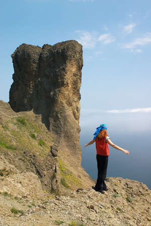 unexplored: Girl standing on the steep in the mountains