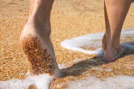 barefoot feet walking in surf on sand coast Stock Photo