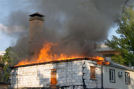 house on fire and clouds of black smoke Stock Photo