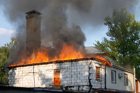 flaming house with clouds of smoke above it