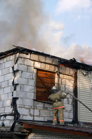 firefighter extinguishing a fire in flaming house