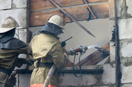 Firefighter with firehose spraying water in window of flaming house Stock Photo