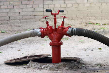 red firecock with connected firehose Stock Photo