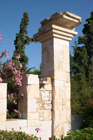 shambles: ancient ruin of stone column in the middle of flowers and trees Stock Photo