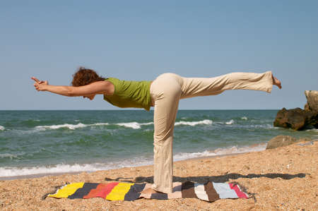 girl doing virabhadrasana yoga pose at sea coast