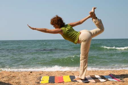 girl doing Natarajasana yoga pose on the seaside photo
