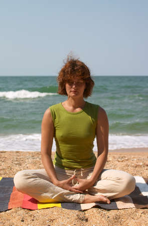 girl meditating on the sea coast sitting  in yoga asana padmasana photo