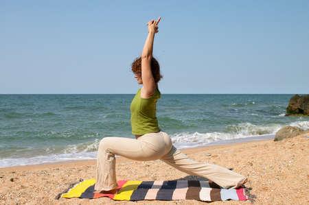virabhadrasana: woman practice yoga asana virabhadrasana at seaside