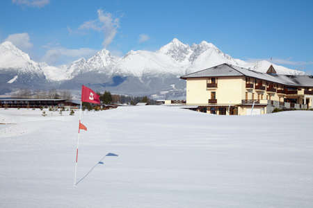 Snow on golf field and mountains at background Stock Photo