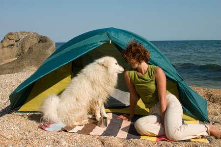 hiker girl and samoyed dog near of tent Stock Photo