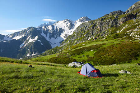 bivouac: Mountaneer bivouac on meadow in mountains Stock Photo