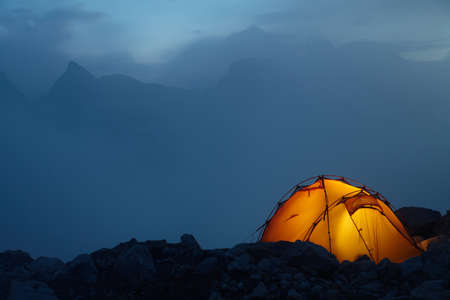 Evening in the Caucasus mountains and orange tent on a stones