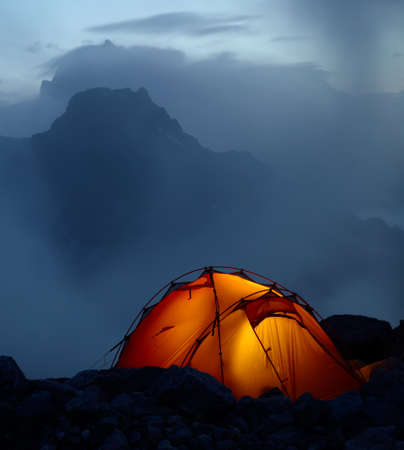 Twilight in the mountains and orange lighting tent