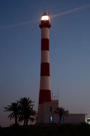 Lighthouse with light beam in the twilight photo