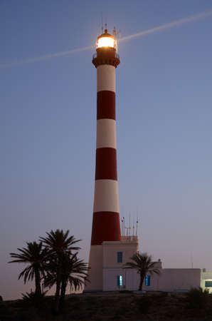 Lighthouse with light beam in the twilight