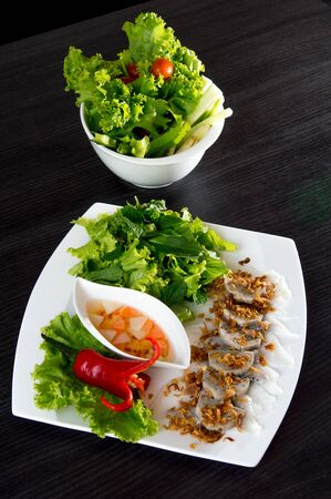 cuon: Vietnamese food  Banh Cuon  dish set on table with vegetable bowl, a rice noodle roll filled with seasoned ground pork Stock Photo