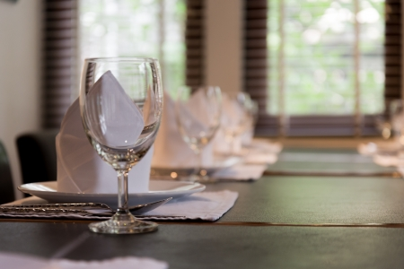 white napkins folded as triangles on plates with wine glass photo