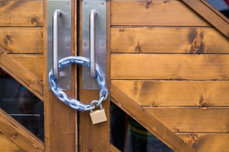 Brass iron lock and chain on wood door photo