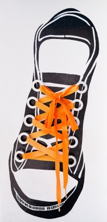 lacing sneakers: orange string tied shoes sneakers wall decorate