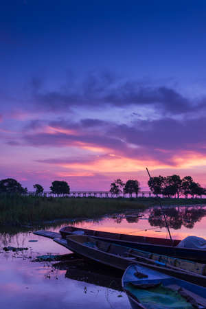 Docked boat on swamp field at dawn with beautiful vivid sky photo