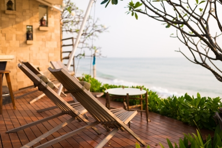 Wooden chairs on balcony of hotel by the beach photo
