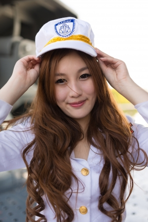 grabing: Pretty woman sailor grabing marine hat expression on battleship Stock Photo