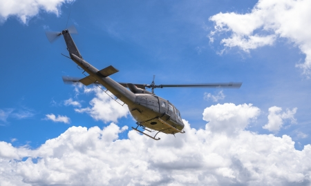 Military helicopter flying through blue sky photo