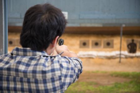 hombre disparando: hombre disparando la pistola para apuntar Foto de archivo