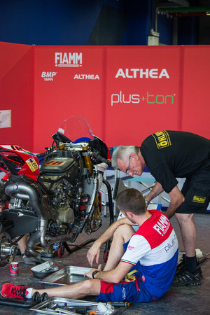 buriram: BURIRAM - MARCH 20 : Althea Racing mechanics inspecting race bike at Chang International Circuit on March 20 2015, Buriram, Thailand Editorial